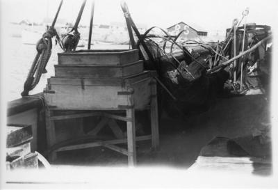'Kattegattexpeditionen 1933: ::  :: Båtdäcket med sålllåda i förgrunden, slädhåv och andra redskap. I fonden syns bebyggelse, hus. ::  :: Ingår i serie med fotonr. 2804-2826.'