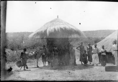 'Diverse fotografier från bl.a. dåvarande Nordrhodesia, nu Zambia, tagna av Konsul Magnus Leijer. ::  :: En grupp kvinnor, män och barn stående framför en mindre cirkelformad byggnad, en man med en åsna, i bakgrunden är ytterligare byggnad och berg synligt.'