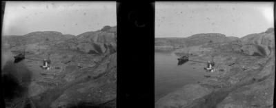 'Bildtext: ''Vid Uttergrytsklubben.'' :: Vy med några människor stående på berghäll ner mot havet där en eka ligger. ::  :: Ingår i serie med fotonr. 5262:1-16. Se även hela serien med fotonr. 5237-5267.'