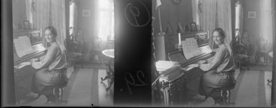 'Bildtext: ''Kjerstin, vid pianot.'' :: 1 kvinna, Kjerstin, sittande vid piano i ett rum. Interiör med möbler, pianopall, bord, stolar, gardiner, fotoramar, prydnadselefant, vas, ljusstake, noter. Kläder. Möbler. ::  :: Ingår i serie med foronr. 5265:1-12. Se även hela serien med fotonr. 5237-5267.'