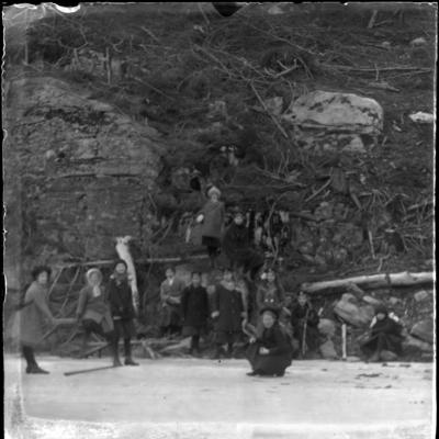 'Gruppbild, drygt 10 barn samlade nedanför bergvägg med liggande träd och grenar. ::  :: Ingår i serie med fotonr. 5415:1-10.'