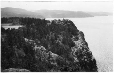 'Bildtext: ''Gullmarsfjorden sydväst om Smörkullen.'' Vy över klädbevuxet berg vid havet. ::  :: Fotonr. 7046:1-84 indelade som ''Landskapsbilder från Göteborgs- och Bohus län.'' Ingår i serie med fotonr. 7046:1-383, 7047:1-33 och 7048:1-67 med bilder från  Länsjägmästare John Lindners bildarkiv.'