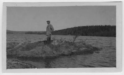 'Storlom, platsen för boet, i sjö. Man stående på liten holme i vattnet. ::  :: Nid.av. 453, Coll.an. 4361. Fynddatum: 1922-05-23. ::  ::  :: Ingår i serie med fotonr. 788-790.'