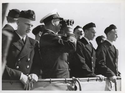En grupp marinsoldater står på bryggan eller vid reling av ett örlogsfartyg. I mitten står en örlogskapten som spana med en kikare.