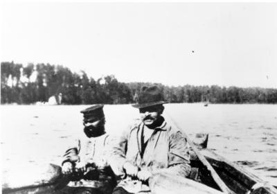 En ny färja har just gått i sjön från tillverkningsplatsen i Östveda och är på väg till Södra Sundet för att tas i drift där. Vid årorna syns från vänster tillverkaren, båtbyggaren Anders Lund tillsammans med Olof Lund.