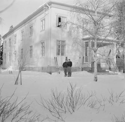 Två militärer vid F 19, Svenska frivilligkåren i Finland står utanför ett hus.