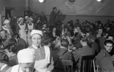 Folksamling. Fika i matsalen vid F 19, Svenska frivilligkåren i Finland. Militärer, civila och kökspersonal vid teaterföreställning.
