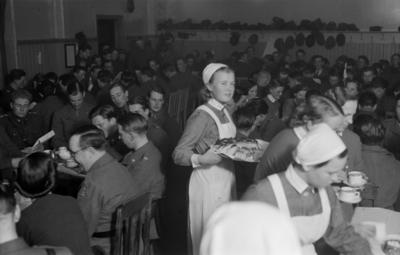 Folksamling. Fika i matsalen vid F 19, Svenska frivilligkåren i Finland. Militärer, civila och kökspersonal. Servering av kaffe och fikabröd.