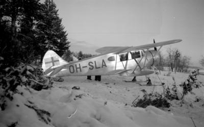 Flygplan Waco ZQC-6 registreringsnummer OH-SLA står på marken vid F 19, Svenska frivilligkåren i Finland. Vy snett bakifrån.