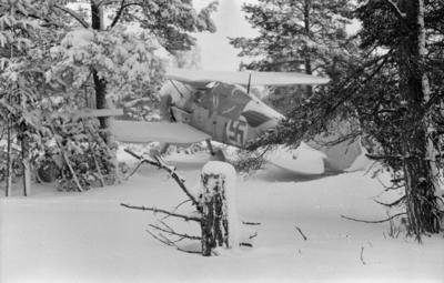 Flygplan Gloster Gladiator tillhörande F 19, Svenska frivilligkåren i Finland, står i fält, inför reparation. Vy bakifrån.