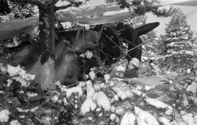 Flygplan Hawker Hart märkt svart M vid F 19, Svenska frivilligkåren i Finland, förbereds för bombanfall. En flygtekniker i arbete vid flygplanet, vilket är kamouflerat i terräng.