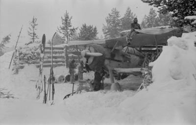 Flygplan Gloster Gladiator gul L i flygplansvärn vid F 19, Svenska frivilligkåren i Finland. Fyra militärer i arbete med flygplanet.
