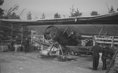 Flygplan Hawker Hart blå R står i värn och lastad med bomber under varmkörning inför start. Vid F 19, Svenska frivilligkåren i Finland, den 23 januari 1940. Militärer i arbete med flygplanet. Åke Mörne och Björn Bjuggren i flygplanet.