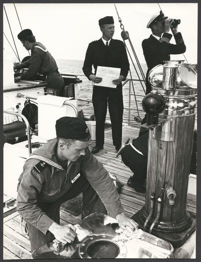 Bilden visar olika sysselsättningar ombord på en av Marinens skolfartyg Gladan eller Falken. I förgrunden putsa en kadett en metall luka, en kapten spåna med kikare och centrum står en sjöofficerare med en sjökarta i handen. De båda verka håller på med navigation.