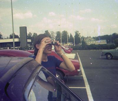 Elina Holkka valokuvaa parkkipaikalla