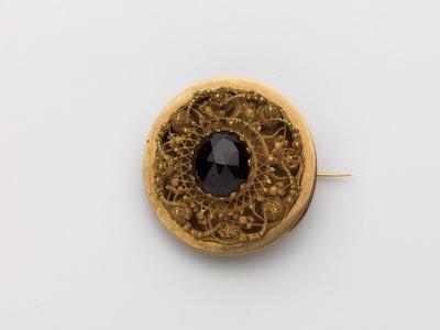 Gouden broche met granaat en ajour cantillewerk in ronde vorm