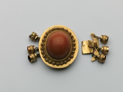 Ovaal gouden collierslot met grote ovale bloedkoraal en rondom zeeuwse knoopjeskrans