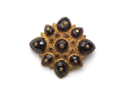Stervormige gouden broche met acht peervormige granaten en zes ronde smaragden en cantillewerk