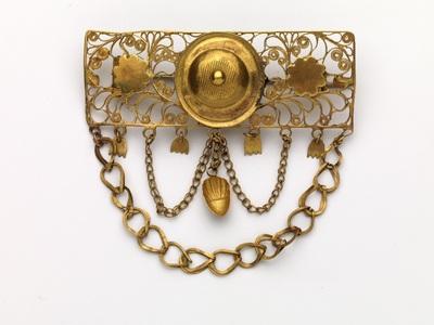 Gouden broche in rechthoekige vorm met aan andere zijde twee kettinkjes, eikeltjes en bloemen gehangen