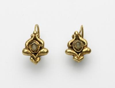 Paar gouden oorringen, stampwerk, waarin een kleine diamant gevat