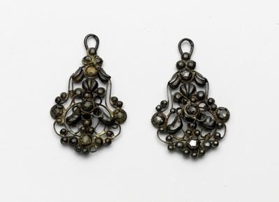 Paar oorbellen met rosetjes en kleine diamantjes, één haak ontbreekt