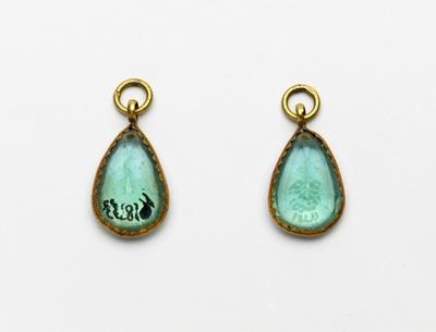 Paar gouden hangertjes, waarin een blauwe transparante steen