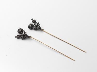 Paar gouden mutsenspelden, diamant waarop in zilver gevatte diamantjes in de vorm van een bloemtak