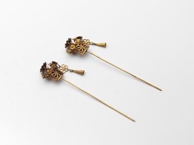 Paar gouden mutsenspelden met knoppen met bloemen, waaraan hanger