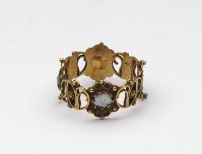 Gouden ring, opengewerkt met schildjes waarin een diamantje