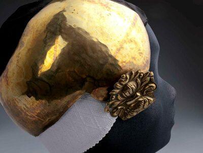 Een koperen oorijzer met gebombeerde oorknoppen in de vorm van een bloemversiering