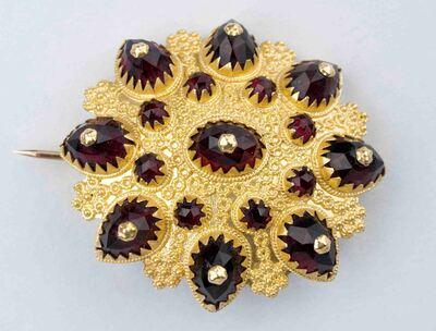 Broche van filigrain goud op massieve achterzijde en op de bovenkant rode granaatstenen waarij op de buitenste rij daarvan goud op de top