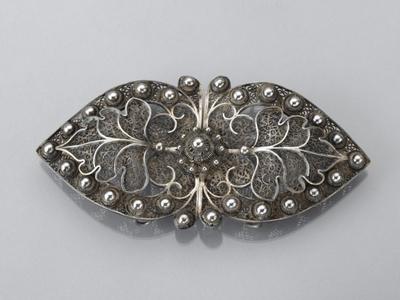 Twee hartvormige zilveren filigraingespen, midden op de haaksluiting een Zeeuws knoopje