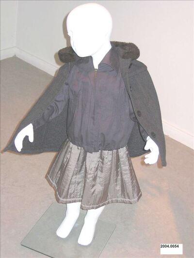 Kinderensemble bestaande uit : cape, bloes en rok.