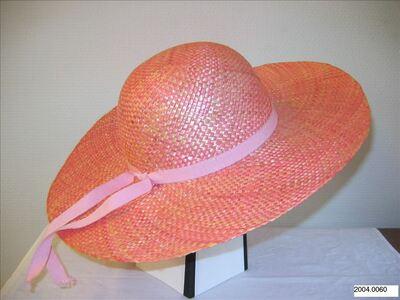 Hoed in roze stro met ronde bol en brede randen