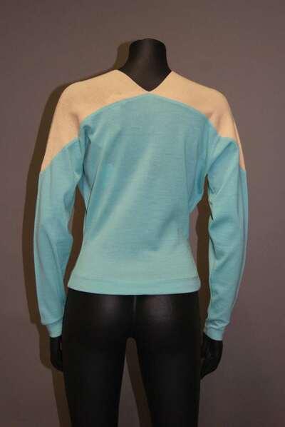 Maglia in lana bicolore nei colori del panna e turchese, scollo a V, modello
