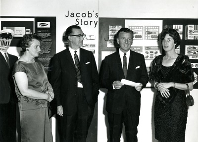 Gordon Lambert and four unknown individuals standing in front of a Jacob's display