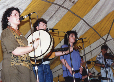 Unidentified [O'Malley], singing and playing bodhran ; unidentified [O'Malley], singing and playing guitar ; unidentified [O'Malley], singing ; unidentified, low whistle ; Fergal Mullen, fiddle performing on stage in Providence, Rhode Island, USA, [1990]