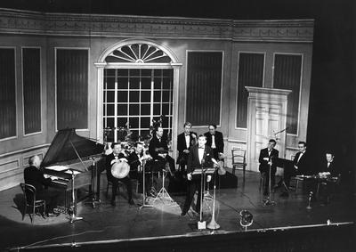Ceoltoirí Chualann [Sean Ó Riada, harpsichord ; Peadar Mercier, bodhrán ; Éamonn de Buitléar, accordion ; Martin Fay, fiddle ; Sean Keane, fiddle ; John Kelly, fiddle ; Sean Potts, whistle ; Michael Tubridy, flute ; Paddy Moloney, uilleann pipes ; Sean Ó Se, singer] seated on stage [possibly the Gaiety Theatre, Dublin]