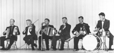 Unidentified ceilí band [Mike Madden, accordion ; John McGreevy, fiddle ; Kevin Keegan, accordion ; James [Jim] Neary, fiddle ; Kevin Henry, pipes ; Billy Soden, drums] playing on stage at the ceilí band competition, Fleadh Cheoil Chicago, 1966