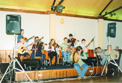 Paul Doyle, guitar ; Tom McDonagh, bouzouki ; Terry Crehan, fiddle ; Roma Casey, fiddle ; Peter Gallagher, accordion ; Eileen Murphy, fiddle ; Seamus Weldon [son of Liam Weldon], bodhrán performing on stage in Club na Muinteoirí, Parnell Square, Dublin, May 1999