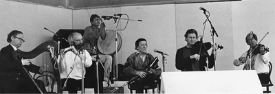 The Chieftains [Derek Bell, harp ; Matt Molloy, flute ; Kevin Conneff, bodhrán and gong ; Paddy Moloney, uilleann pipes ; Sean Keane, fiddle ; Martin Fay, fiddle] performing on stage