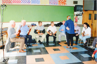 Joe Ryan, Peadar O'Loughlin, Joe Rynne, Michael Kelleher, Vincent Griffin, Maire O'Keeffe, seated in a classroom playing fiddles, Presentation Convent Secondary School, Spanish Point, Co Clare, during the Willie Clancy Summer School, July 2001