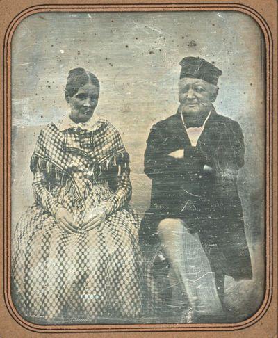 Bildnis eines älteren Ehepaars, ganze Figuren, sitzend, sie in kariertem Kleid, er mit Fez, Arme verschränkt und Beine übereinandergeschlagen