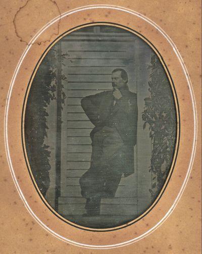 Herr, in der Sonne vor einer weißen Türe auf der Gartenseite eines Hauses stehend