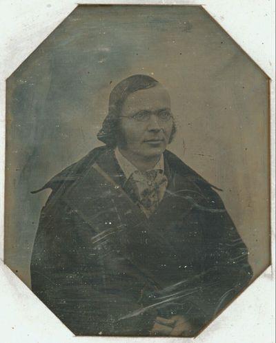 Bildnis eines jungen Mannes mit Brille, halbe Figur, im Mantel