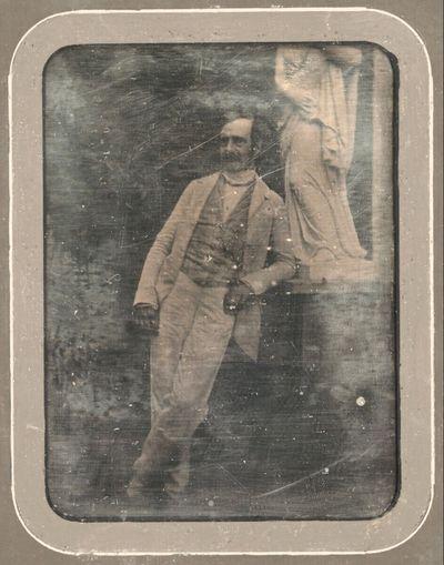 Bildnis eines bärtigen Herrn in hellem Sommeranzug über gestreiftem Gilet, der an das Postament der Statue einer antikisierenden weiblichen Figur gelehnt steht