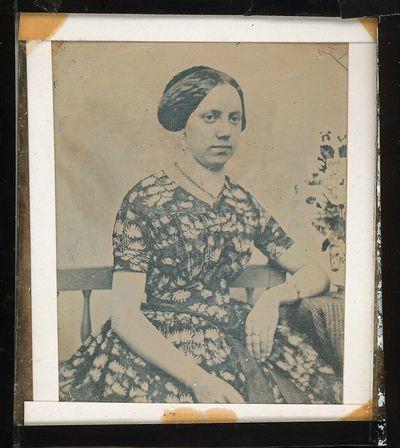 Bildnis einer jungen Dame im Sommerkleid, an einem Tisch mit Blumenvase sitzend