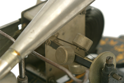 Puck phonograph: view of the governor weights and the thin metal bar supporting the horn and reproducer