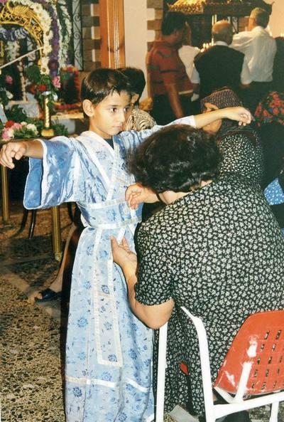 Η παπαδιά ντύνει ένα από τα νεαρά αγόρια που θα συνοδεύσουν την περιφορά του επιταφίου της Αγιάννας.