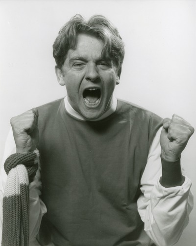 black and white photograph of a man with clenched fists and a striped scarf around his wrist